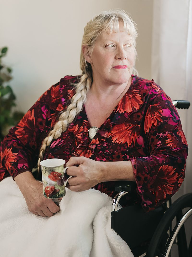 An EQC patient sitting in a wheelchair drinking out of a mug