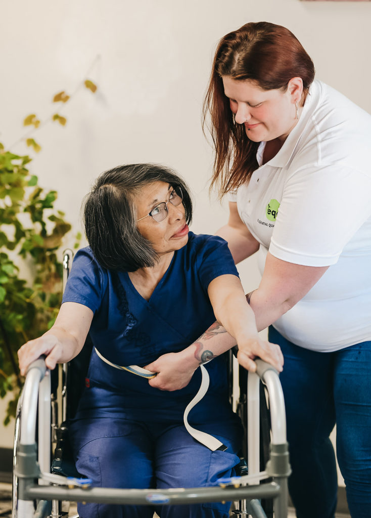 An EQC caregiver helping a patient use a walker